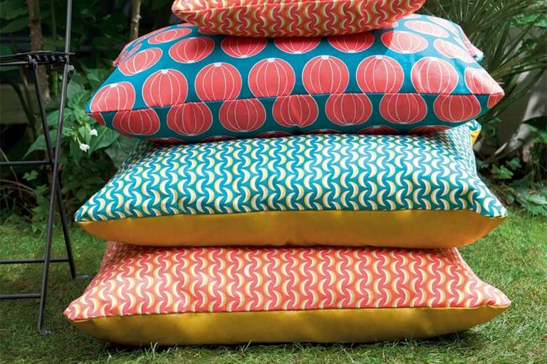 Stack of large outdoor cushions on grass