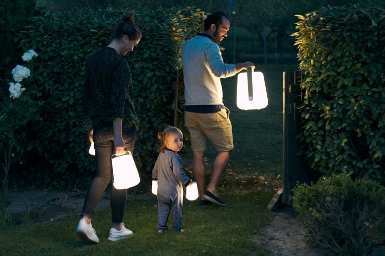 A family walks with Fermob Balad Lamps at night