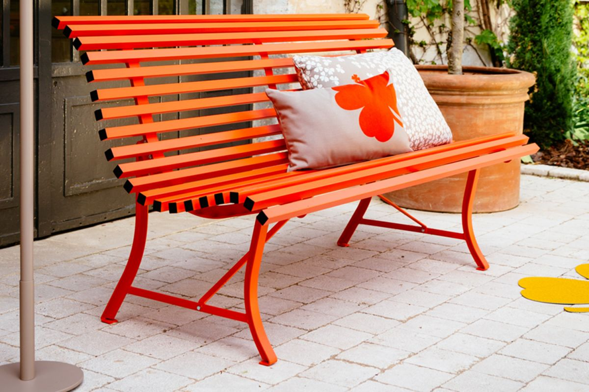 Metal garden bench in orange colour sitting in a courtyard