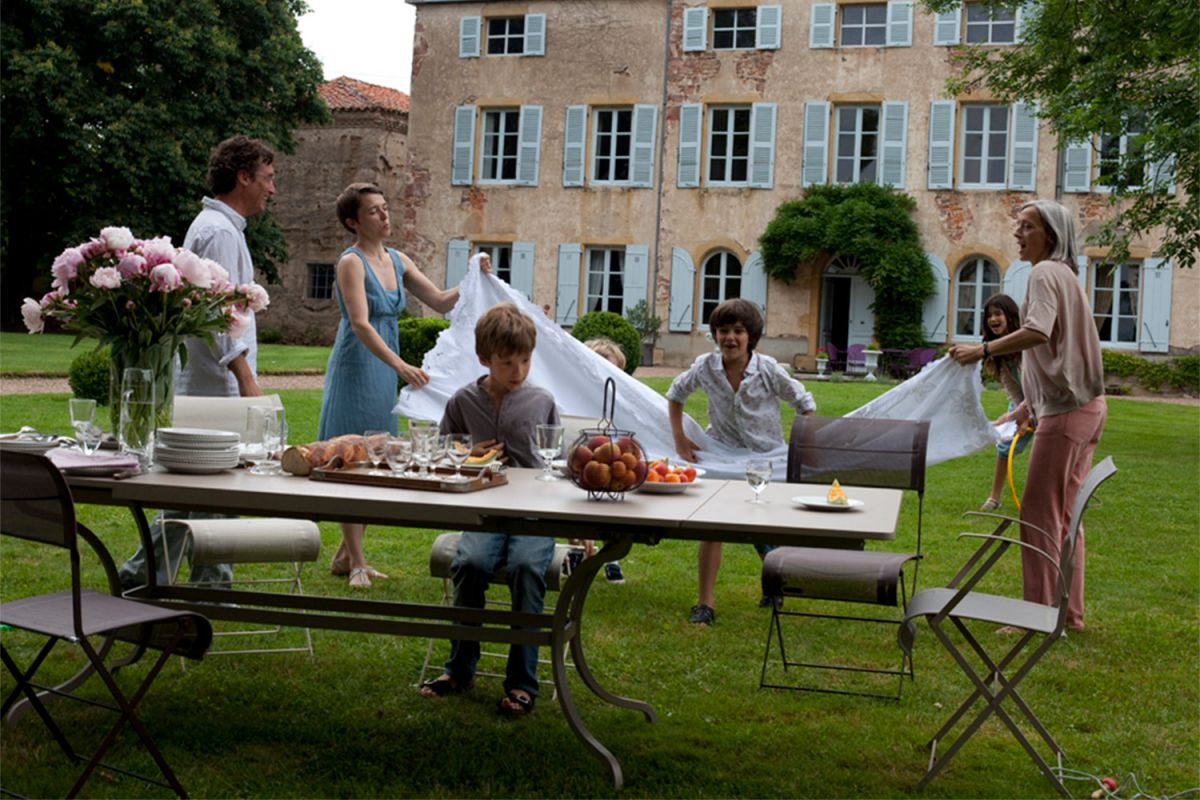 Fermob Romane extendable outdoor table in Nutmeg colour with a family in front of French chateau