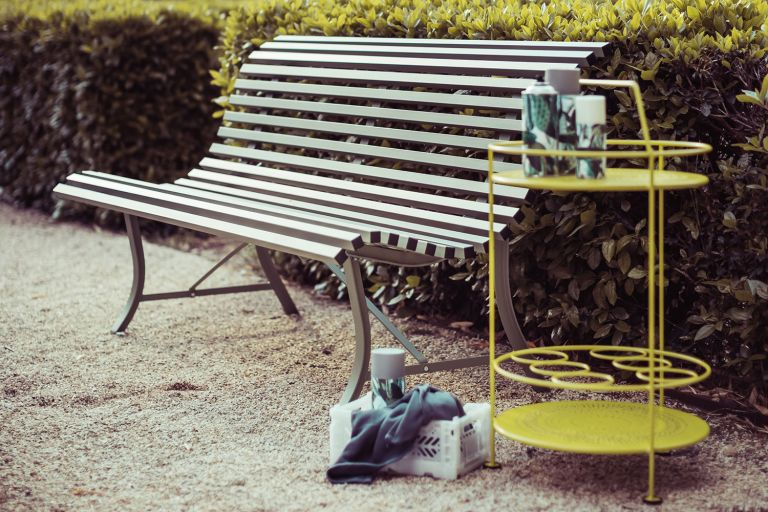 Fermob Louisiane garden bench on a gravel pathway in Nutmeg with Fermob Montmartre side bar table