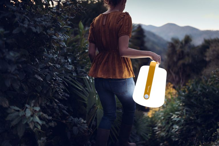 Woman carrying Fermob Balad outdoor light through garden path at night