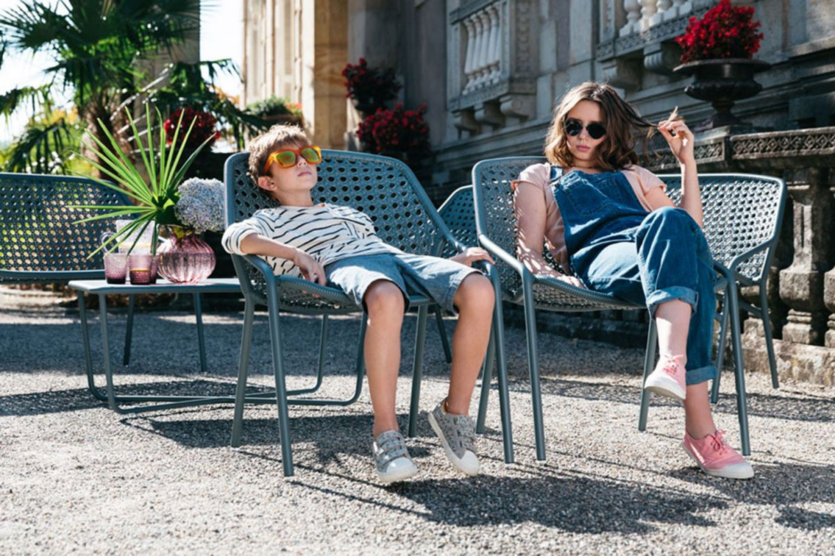 Fermob Croisette outdoor armchairs in storm grey by a chateau with kids