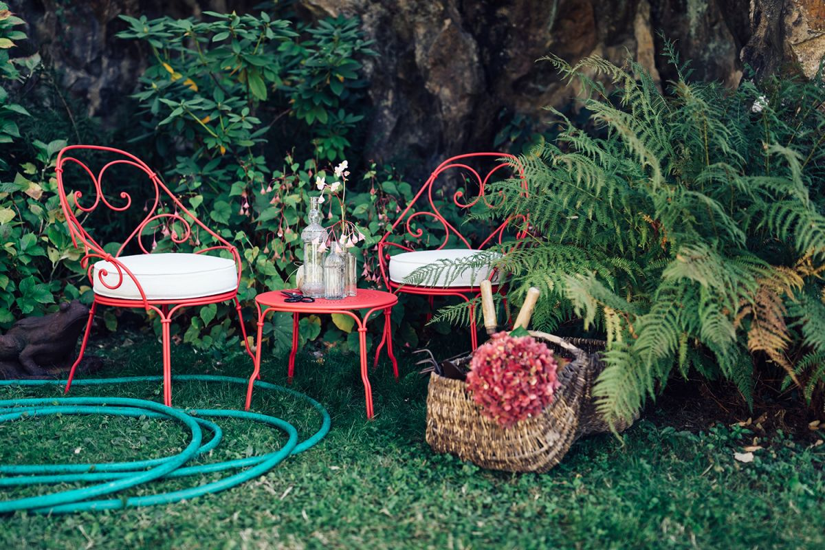 French Cabriolet Iron Outdoor Armchairs And Side Table In A Garden