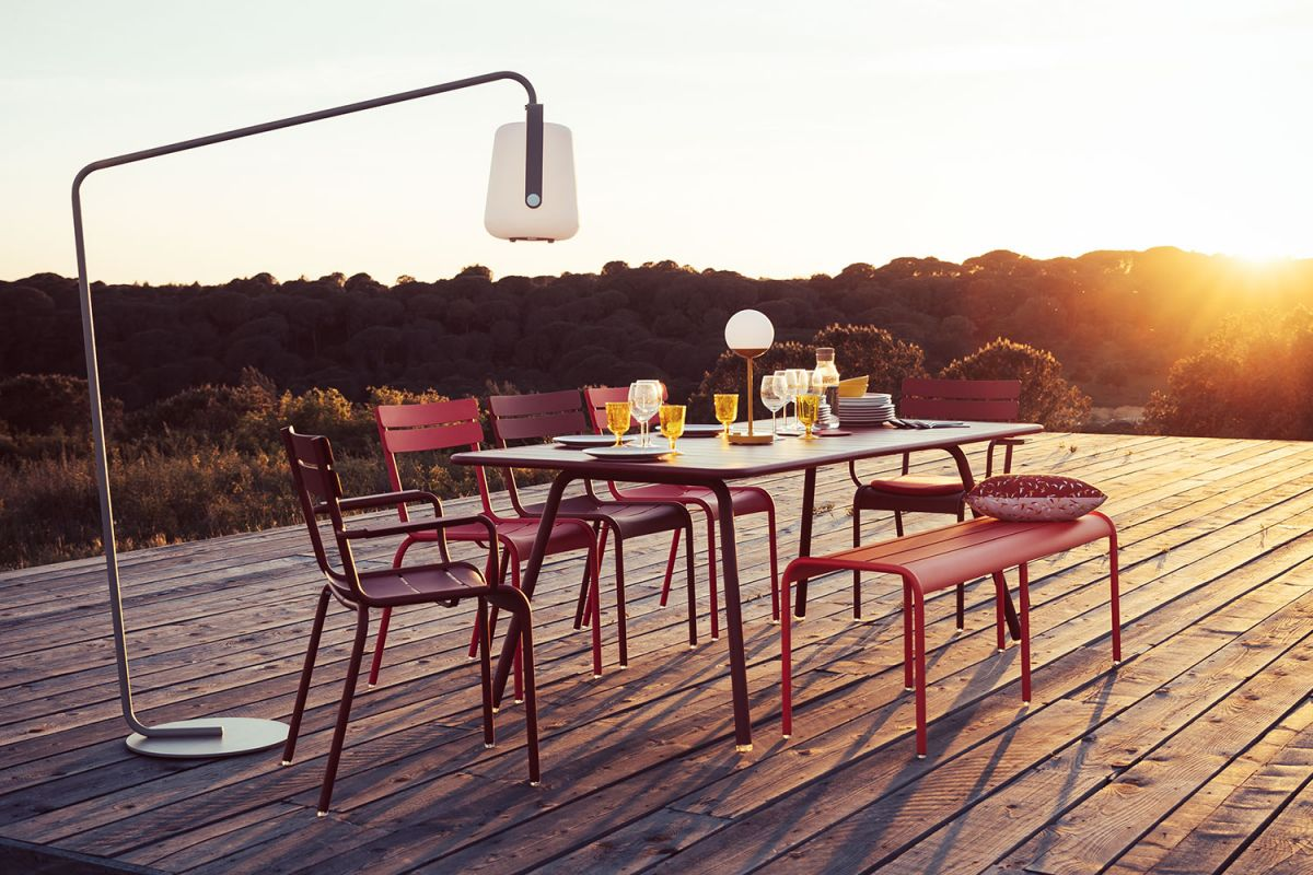 Fermob Luxembourg 8 place outdoor dining setting with bench at sunset under Fermob Balad outdoor lamp on a stand