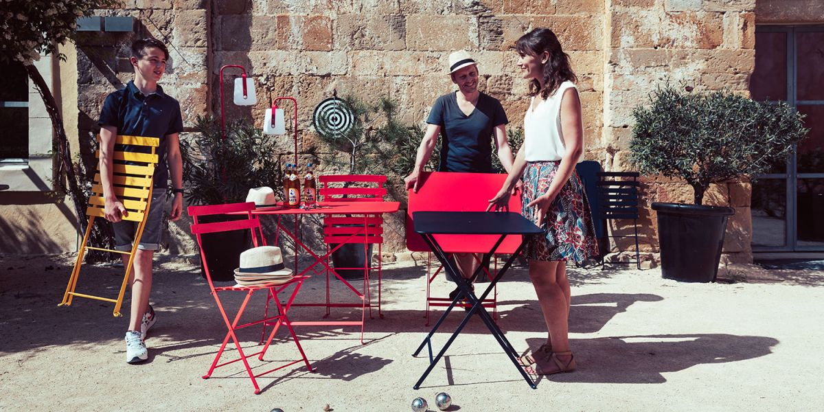 Three people set out bright Fermob Bistro folding square tables and chairs in the sun for a game of boules
