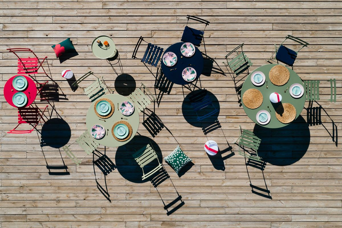 Aerial view of Fermob Bistro cafe folding chairs and round tables set out on a decked area