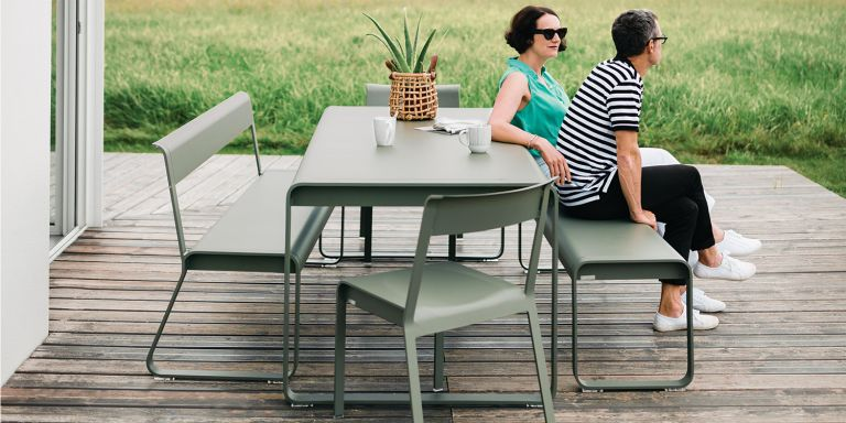 Man & woman enjoy a coffee on Fermob Bellevie modern outdoor dining table with benches and chairs