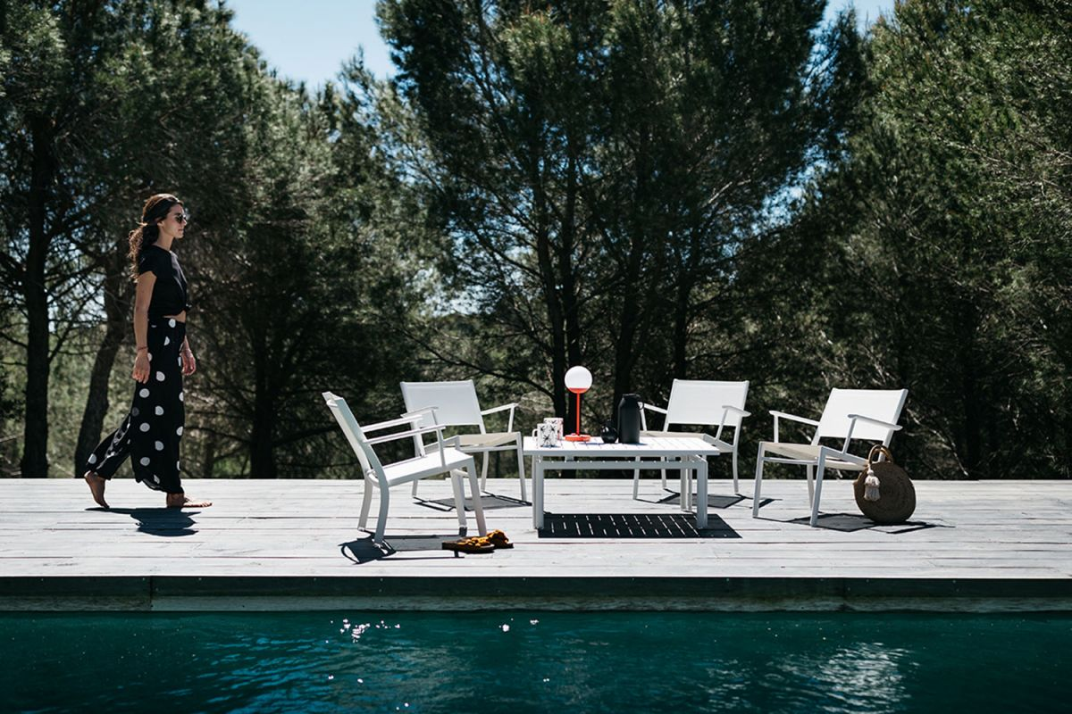 Woman walks towards a Fermob Costa outdoor low armchair setting in white with a coffee table by the pool