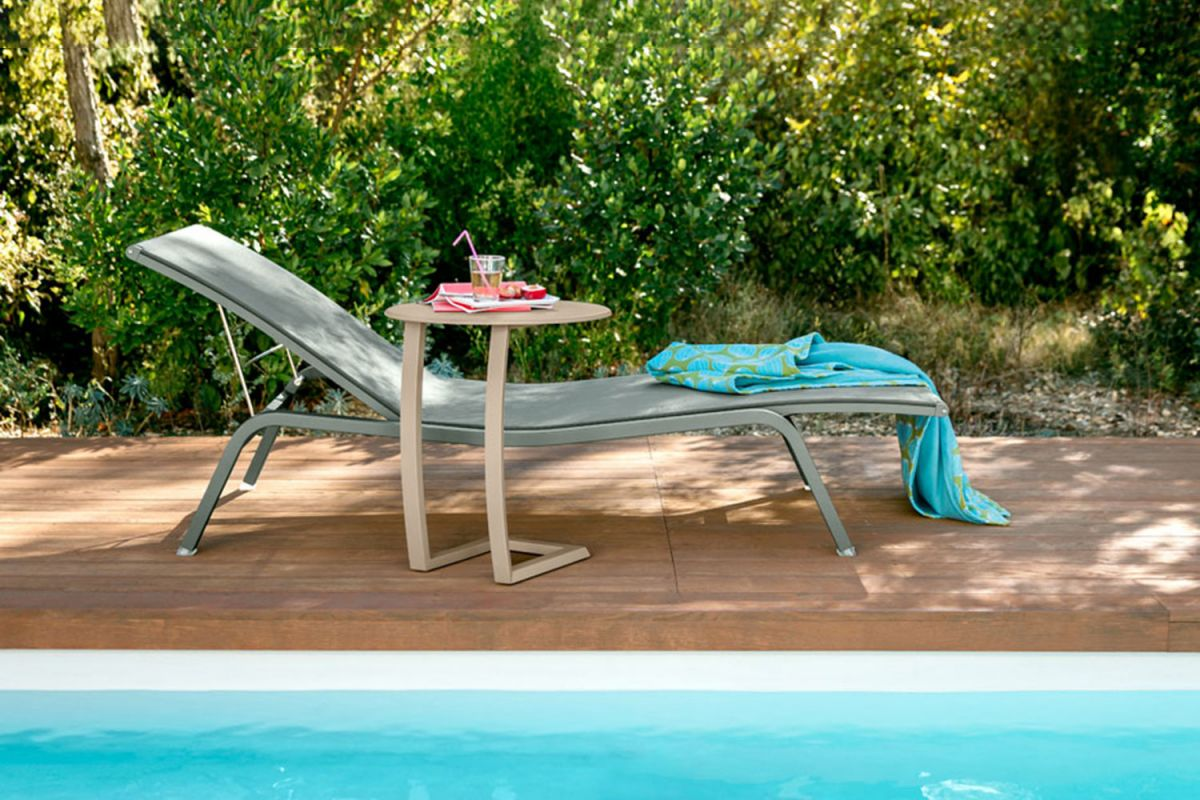Fermob Alize XS Sunlounger in Cactus with offset side table in Nutmeg sits by pool