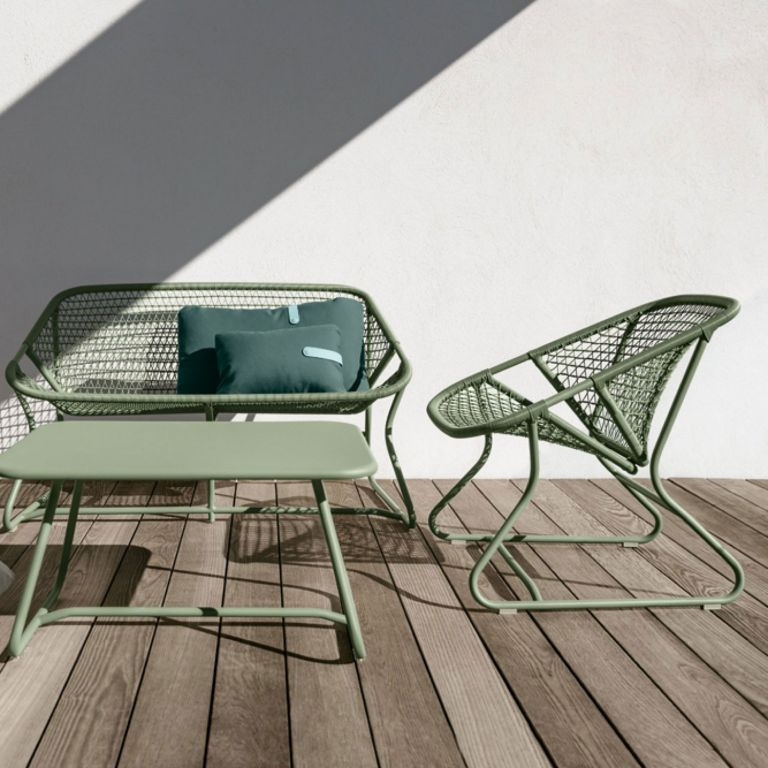 Fermob Sixties Cactus coloured casual outdoor chairs and coffee table in front of a rendered wall