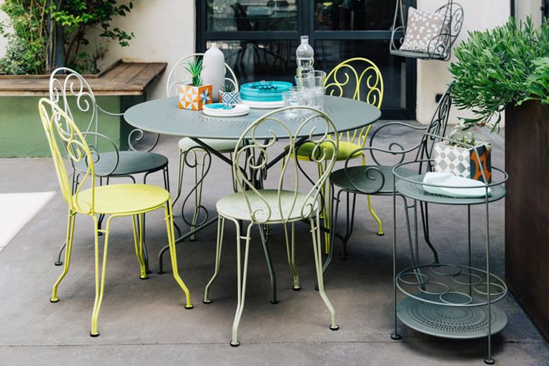 Fermob Montmartre metal French chairs and large round table sit in a modern courtyard