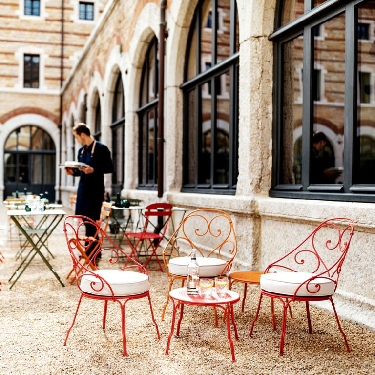 Colourful Fermob French metal outdoor furniture sits on gravel in cafe courtyard