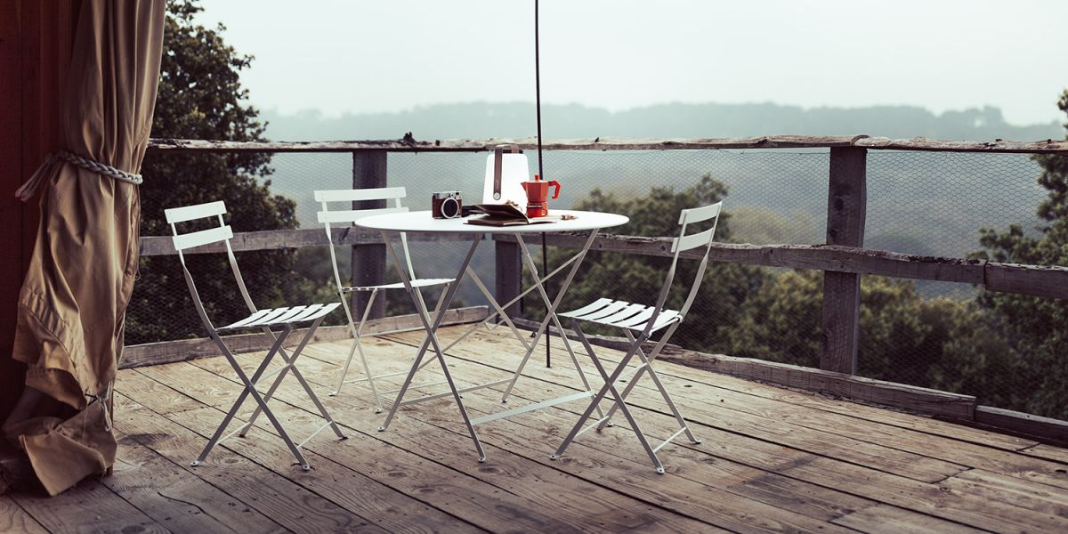 A Fermob Bistro 96cm metal folding round table and chairs in Cotton White sit on a rustic deck