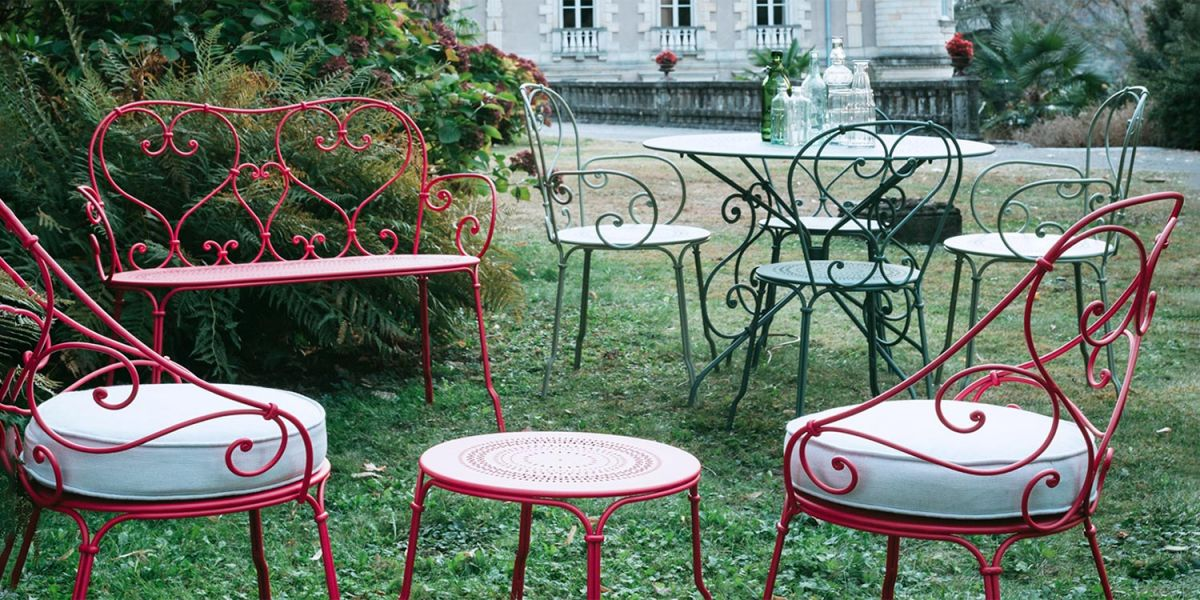 Fermob 1900 French metal garden furniture sits on grass in front of a chateau
