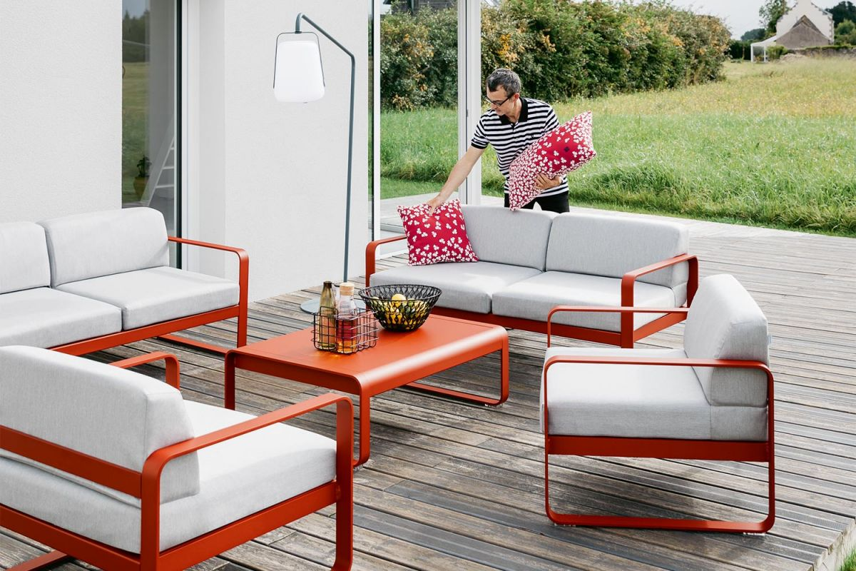 Man places cushion on Fermob Bellevie Two Seater Outdoor Sofa in Chilli colour on a residential house deck
