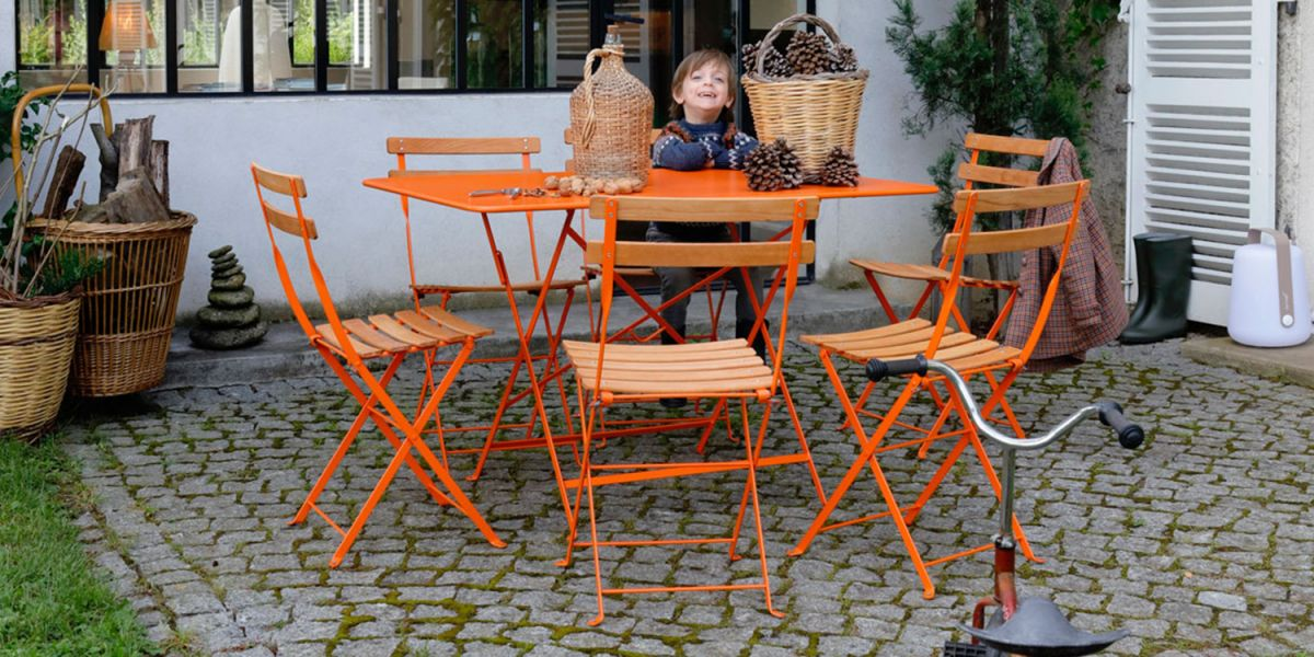 Child sitting at folding rectangle outdoor table in orange colour with six dining chairs