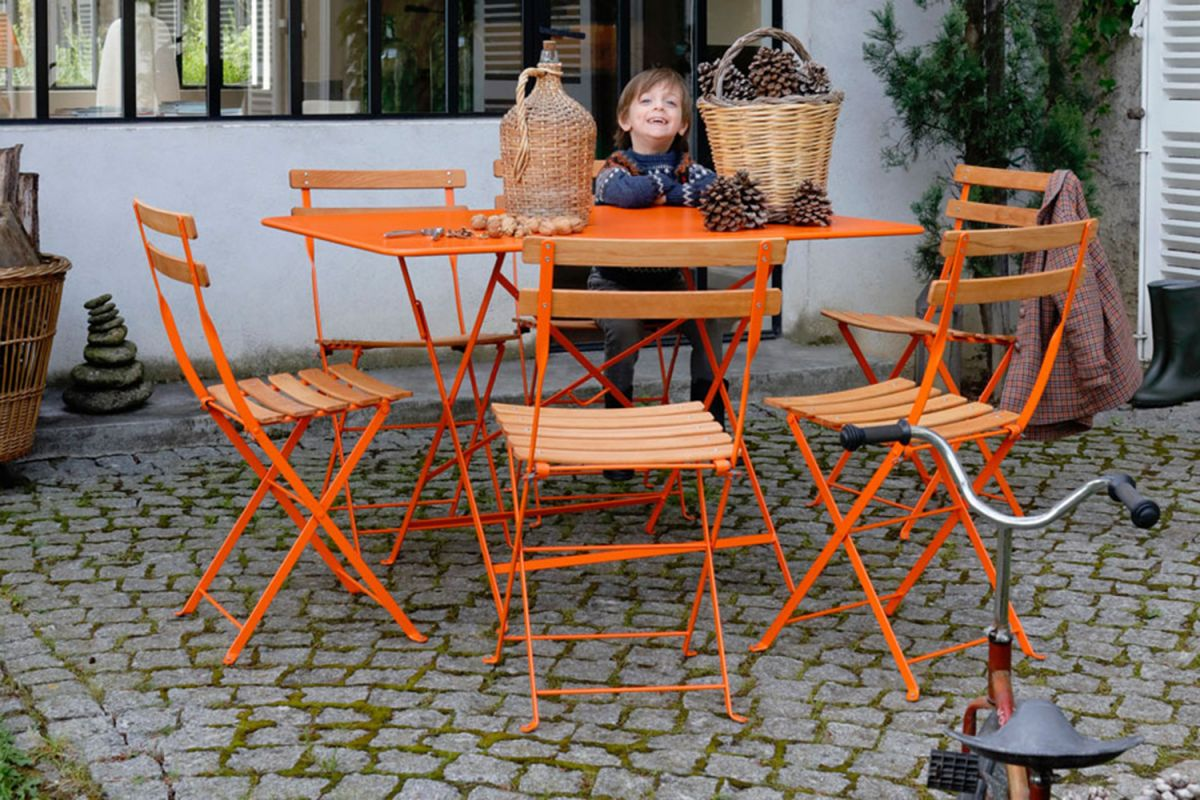 Child sitting at Fermob folding rectangle outdoor table in orange with six folding Fermob cafe chairs