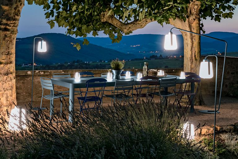 Fermob Ribambelle extending outdoor table in Storm Grey colour sits outside at dusk with 12 seats