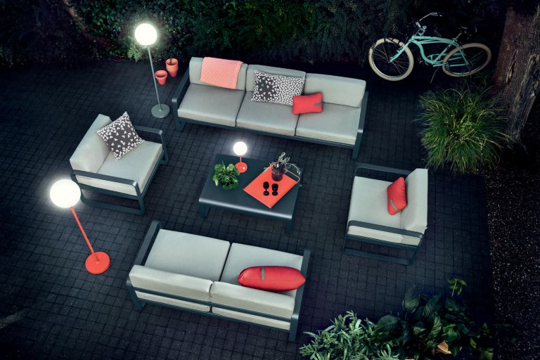 Fermob Bellevie sofa setting in Anthracite on paved courtyard at night lit by Fermob Mooon! outdoor lamp