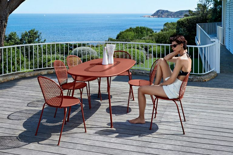 Woman sits at red ochre Fermob Lorette oval outdoor table and chairs on a deck terrace overlooking sea