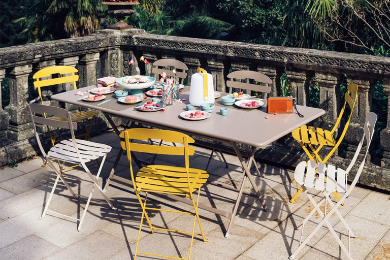 Fermob La Mome folding chairs and Caractere large folding outdoor table on a paved terrace