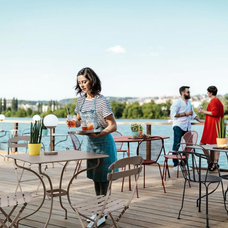 Waiter places drinks on a table in a cafe featuring Fermob commercial outdoor furniture