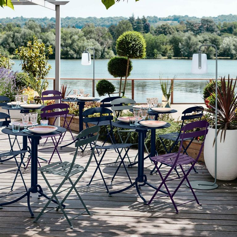 Colourful Fermob La Mome folding chairs and tilting Fermob Ariane tables at a riverside cafe