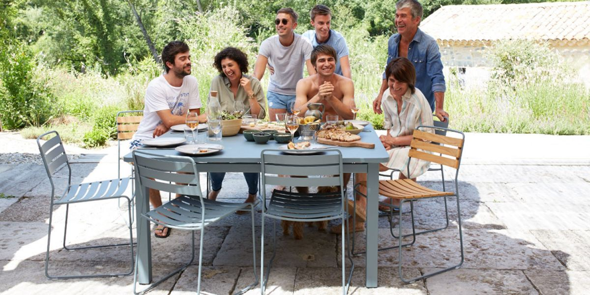 Family sits at square outdoor table enjoying meal