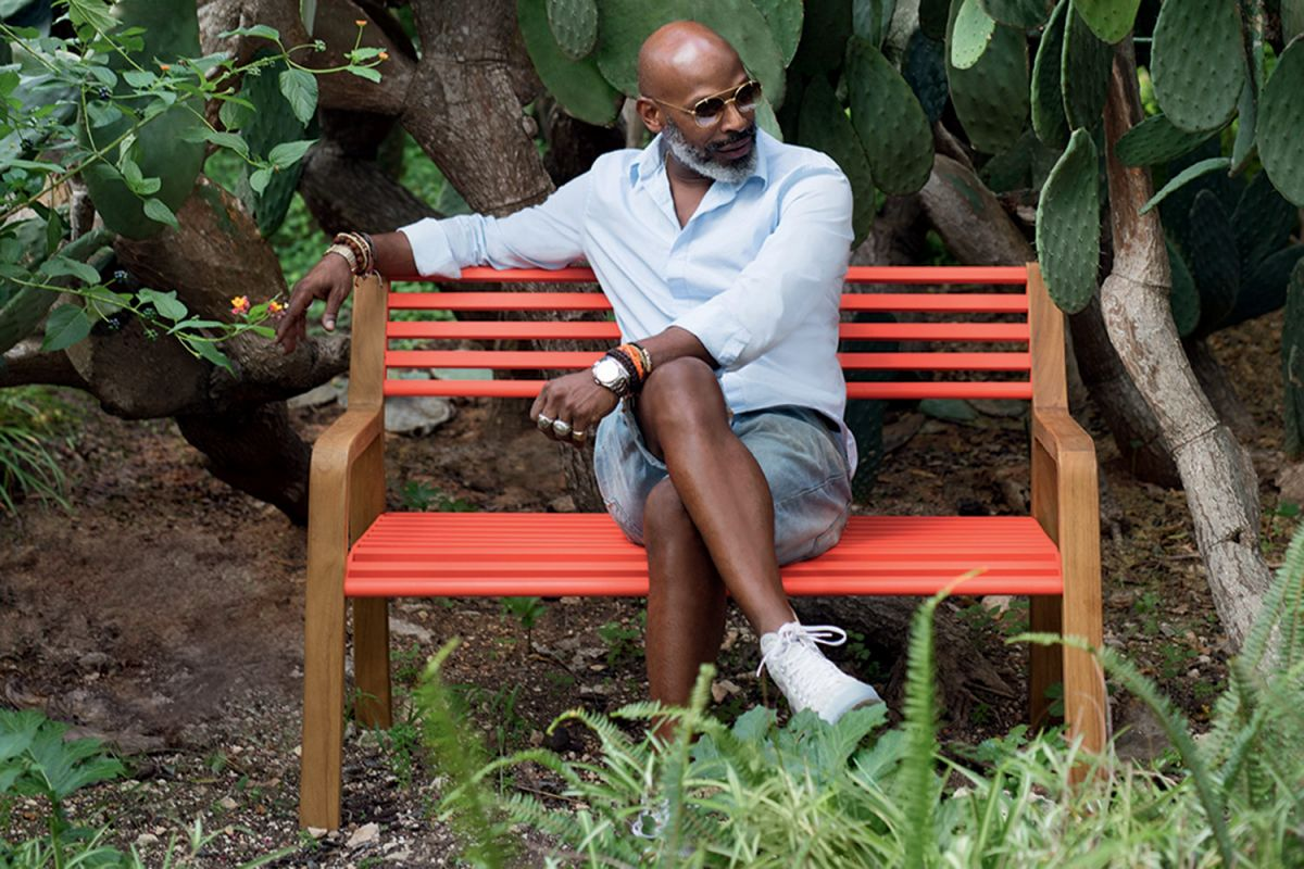 Man sits on Fermob Somerset outdoor bench with Capucine metal slats and teak arms