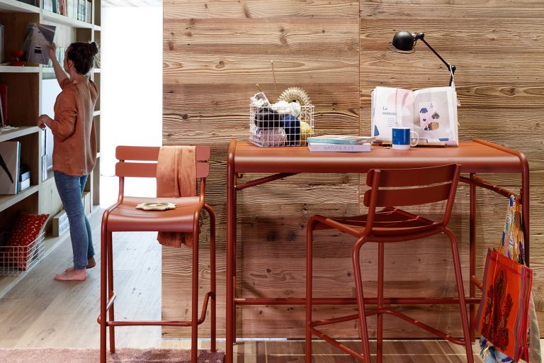 Fermob Luxembourg aluminium high bar table and bar stools in Red Ochre indoors