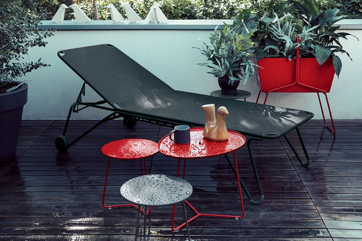 Fermob Harry sunlounge on a decked terrace after the rain alongside some Fermob Cocotte side tables