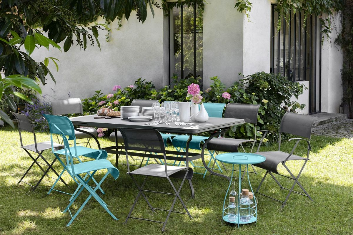 Fermob Romane extending table and a collection of Dune folding outdoor chairs sitting in a garden