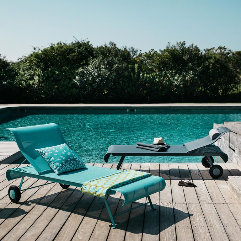A pair of Fermob Dune sun loungers in Lagoon Blue and Storm Grey sitting on decking beside a pool