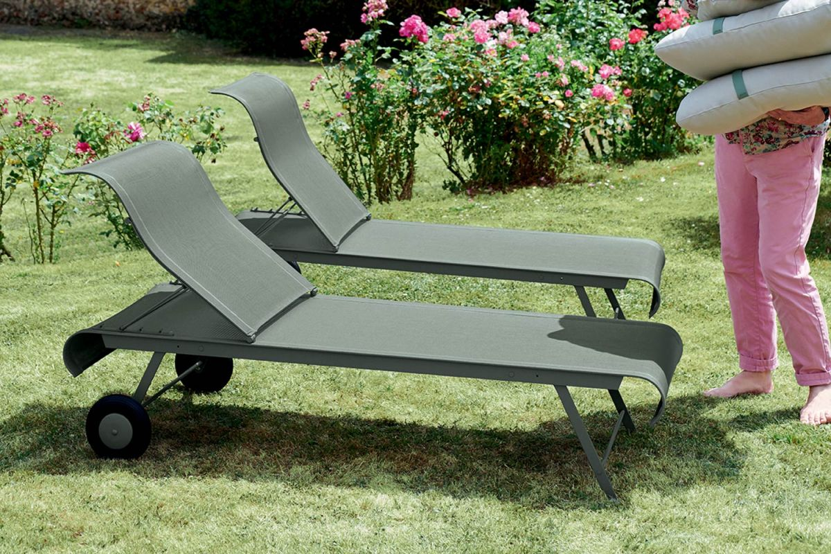 Two Fermob Dune sun loungers sitting on grass in a backyard