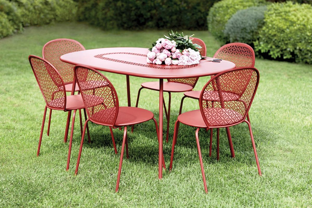 Fermob Lorette oval dining table and six chairs sitting on grass in a garden