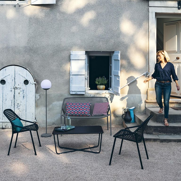 Fermob Croisette casual armchairs, bench and coffee table with Mooon! outdoor lamp in a courtyard
