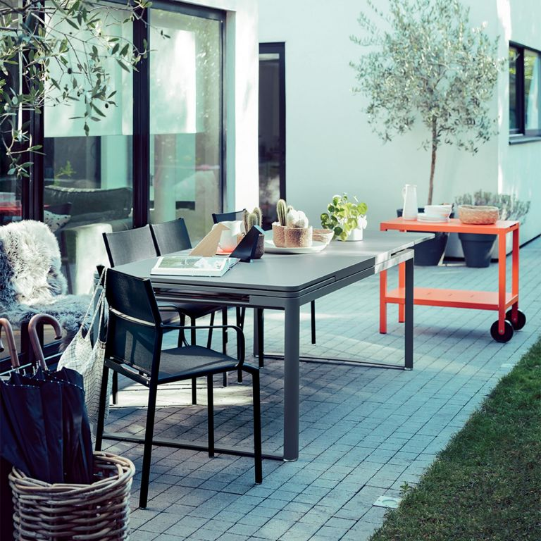 Fermob Biarritz extending outdoor table with Cadiz dining armchairs and a Quiberon bar trolley on a cobbled redidential terrace