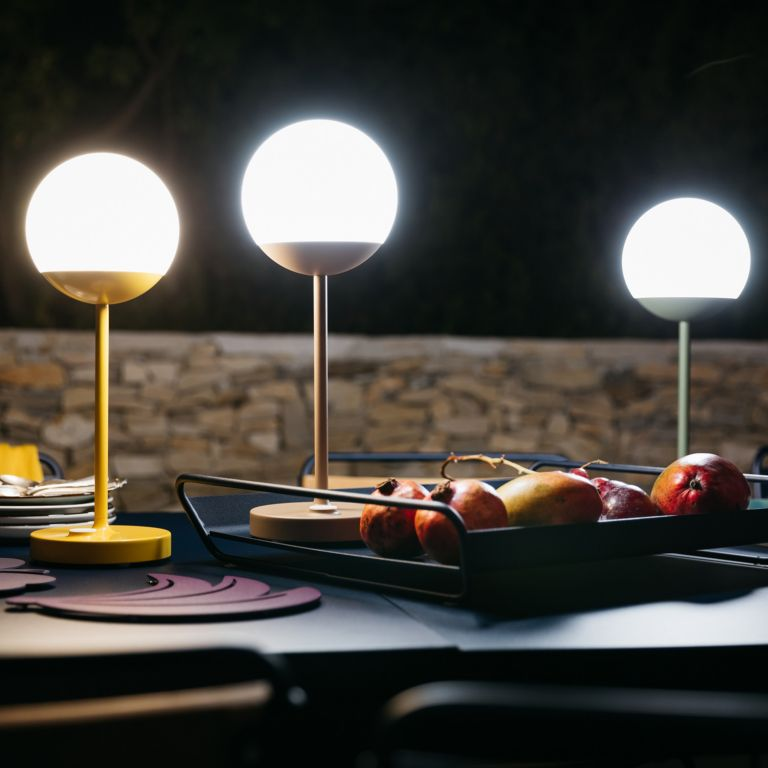 Three Fermob Mooon! LED outdoor lamps light a dining table at night