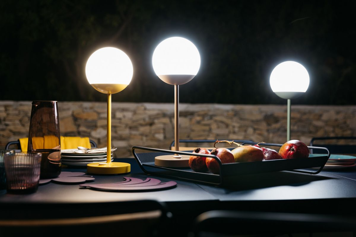 Three LED outdoor lamps sit on a table lit at night