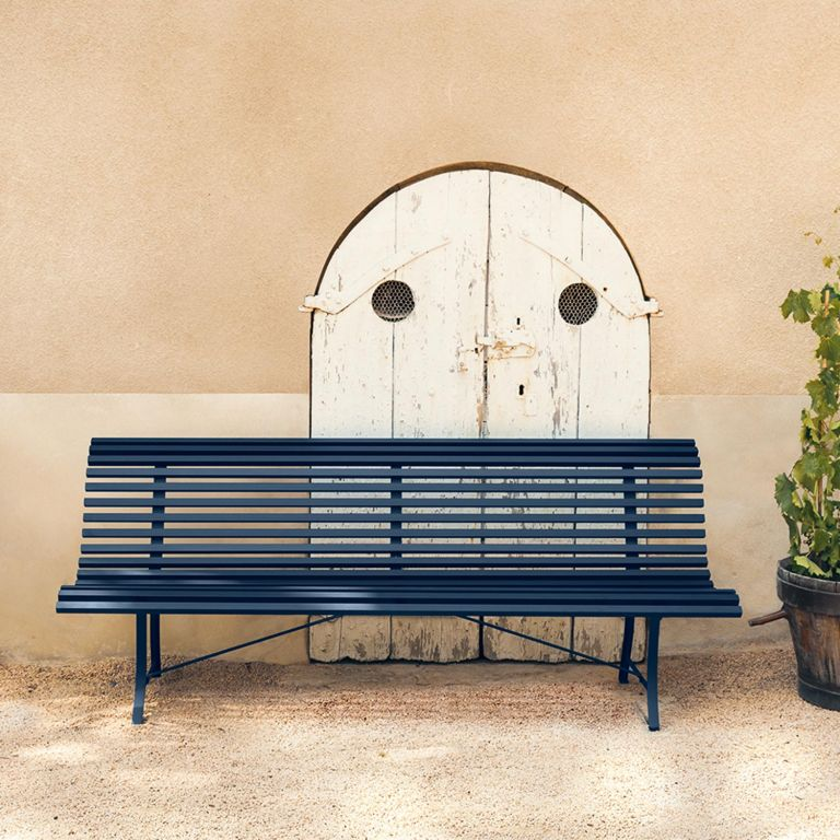 Fermob Louisiane 200cm garden bench in Deep Blue in front of old door