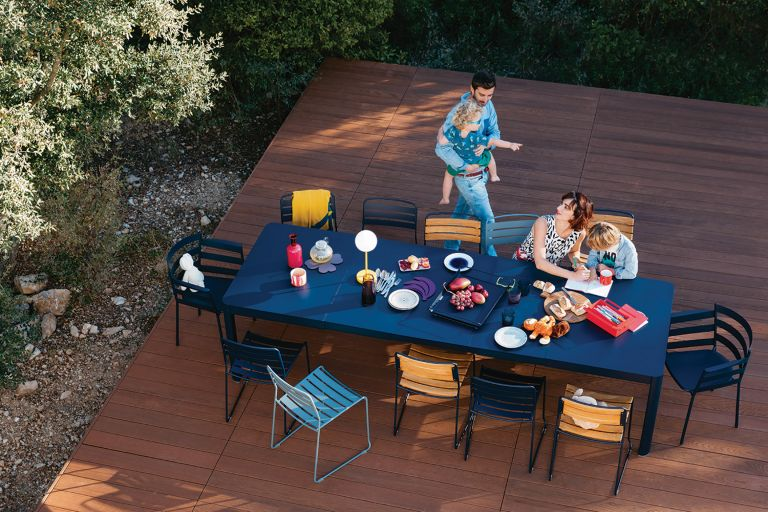 Long extendable outdoor table on a deck with family enjoying food