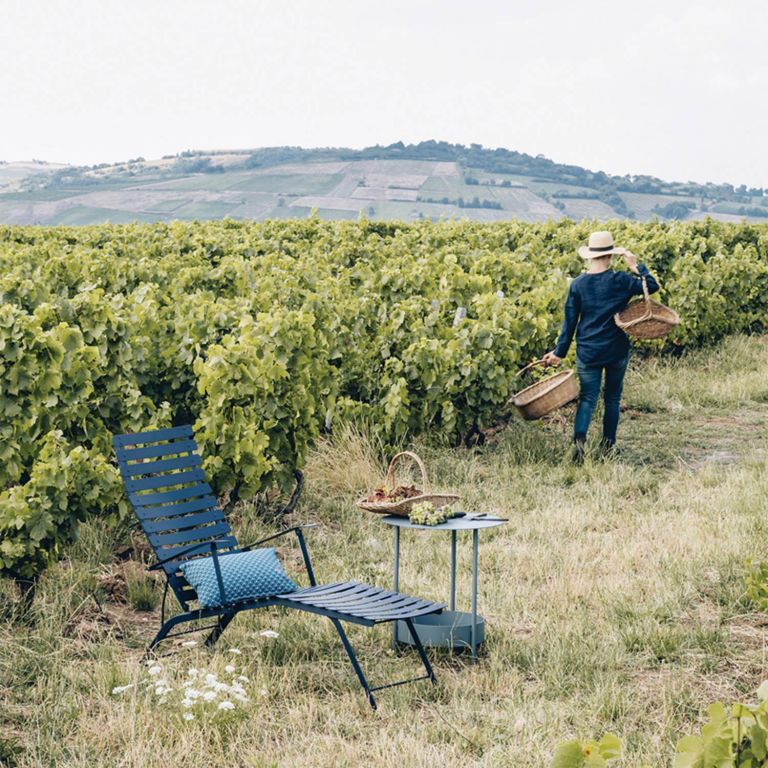 Fermob Bistro Deck Chair in Deep Blue sitting in a vineyard setting