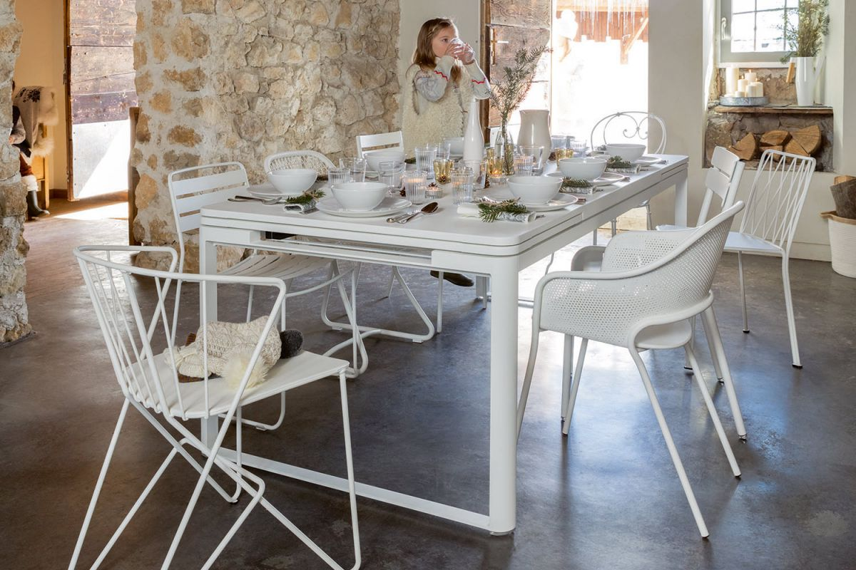 Fermob Biarritz extendable outdoor table in Cotton White surrounded by assorted Fermob chairs