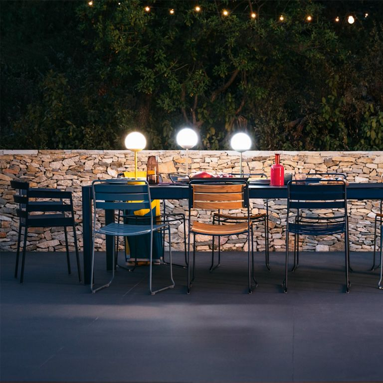 Fermob Ribambelle extending outdoor table looking festive at night in front of stone wall