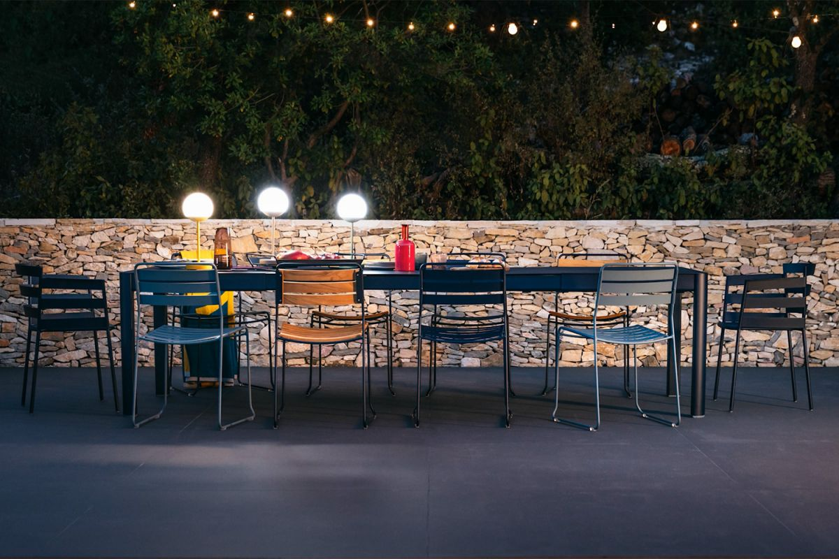Extending outdoor table looking festive at night in front of stone wall